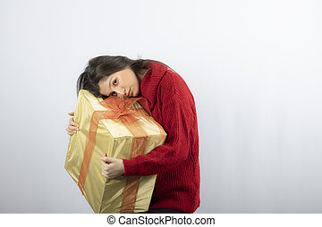 Cute woman in red sweater holding Christmas present