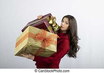 Cute woman in red sweater holding Christmas presents