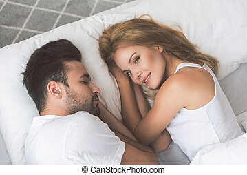 Cute young woman lying on bed near her husband