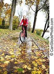 Cyclist ride through a puddle in the autumn park