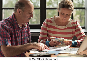 daughter helps her father count money and manage the family budget.