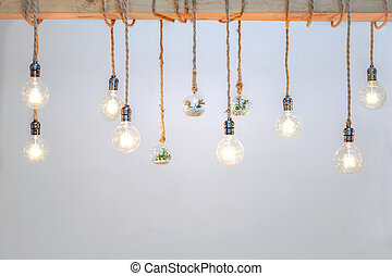 Decorated cozy lamps stick in the rope and little tiny tree with small white rock inside the ball glass hang on to big wood log in front of white background.