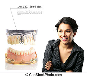 Gorgeous middle age Latin woman next to a close up of model dental Moulage with an implant isolated on white background