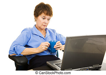 Depressed looking businesswoman staring at her computer. Isolated on white.