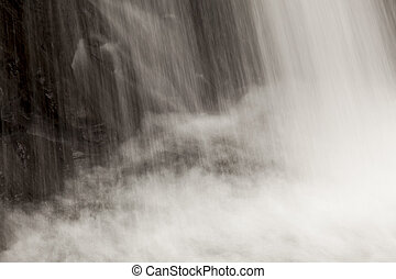 A veil of water falling over rocks at Fish Hawk Falls in Clatsop County, Oregon