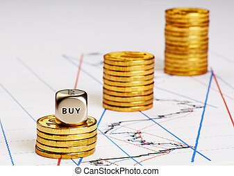 Dices cube with word BUY, stacks of golden coins and a up trend chart as the background. Successful trading. Selective focus