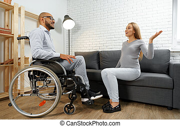 Disabled african american man in wheelchair talking to his pregnant wife in the living room