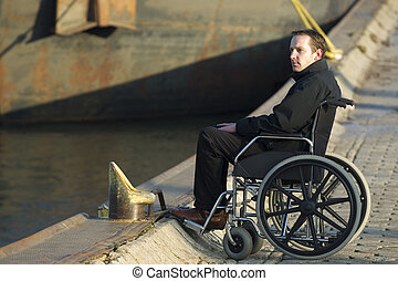 Relaxed disabled man spending some time alone on wheelchair outdoors