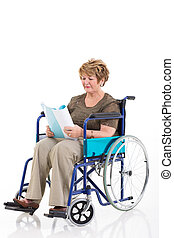 disabled senior woman reading a book on wheelchair