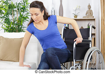 disabled woman in wheelchair moving to the sofa