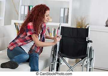 disabled woman trying to sit on wheelchair