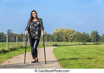 Disabled young woman walking on crutches in park