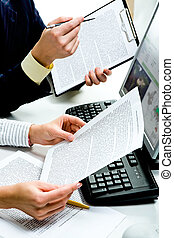 Close-up of businesspeople�s hands holding documents with computer near by