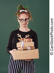 Displeased woman holding stack of christmas present