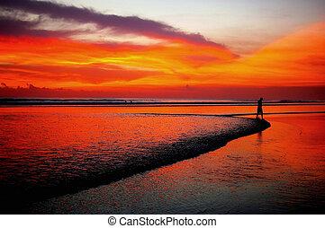 Distant man walking on beach at sunset