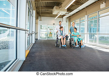 Doctor and nurse pushing patients on wheelchairs at corridor in hospital