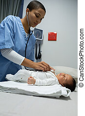 Doctor examining baby with stethoscope in medical examination room