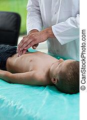 Doctor examining boy stomach