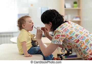 Doctor examining little kid's throat