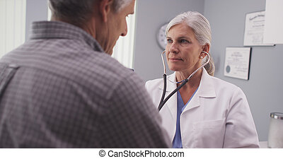 Doctor listening to patient's heart rate with stethoscope