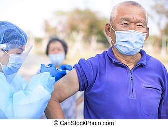 Doctor making injection covid-19 vaccine to senior people