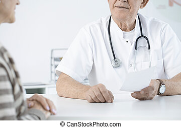 Doctor with stethoscope giving prescription