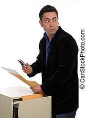 A man slipping documents out of a file cabinet and photographing them