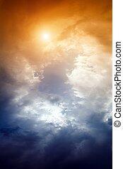 Dramatic impressive background - sky with orange sun and dark clouds