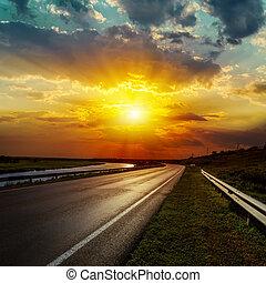 dramatic sunset over asphalt road
