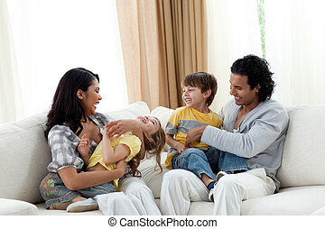 Earing parents playing with their children on sofa