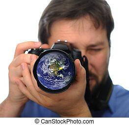 Earth in camera lens, man shooting photo
