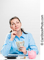 Economical businesswoman dreams where to spend the accumulated money