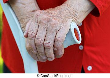 Elderly wrinkled hands holding a crutch