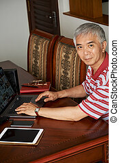 Chinese man working on laptop at home