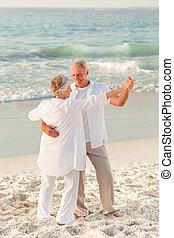 Elderly couple dancing on the beach