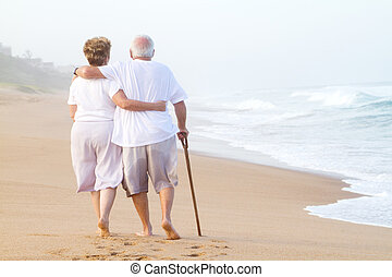 behind view of an elderly couple strolling on the beach together