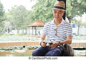 Elderly man checking his camera
