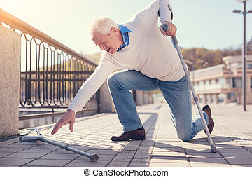 Elderly man reaching for crutch while trying to get up