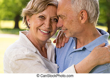 Elderly wife and husband cuddling outdoors