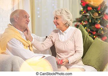 Elderly woman holding christmas present
