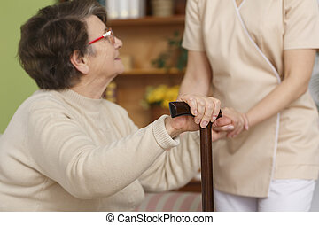 Elderly woman trying to stand up