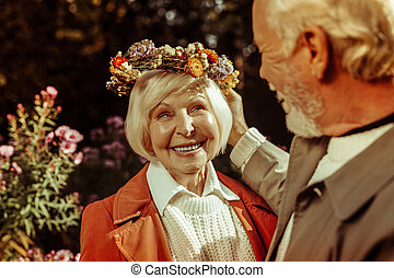 Elderly woman wearing floral wreath and smiling to her husband.