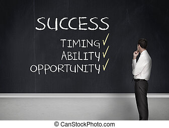 Elegant businessman looking at success terms written on chalkboard
