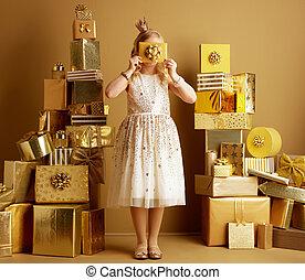 elegant girl holding golden gift card in front of face