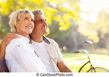 elegant mature couple sitting outdoors