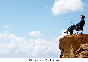 Portrait of businessman sitting on the chair on edge of cliff