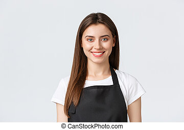 Employees, job employment, small business and coffee shop concept. Cheerful friendly-looking smiling cashier, barista greeting guests in black apron, standing white background