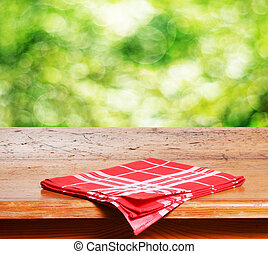 Empty wooden table and fresh green bokeh bubbles in background