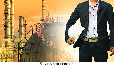 engineering man and safety helmet standing against oil refinery