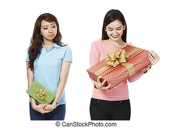 A young woman envious of the much bigger present of a friend (on white background)